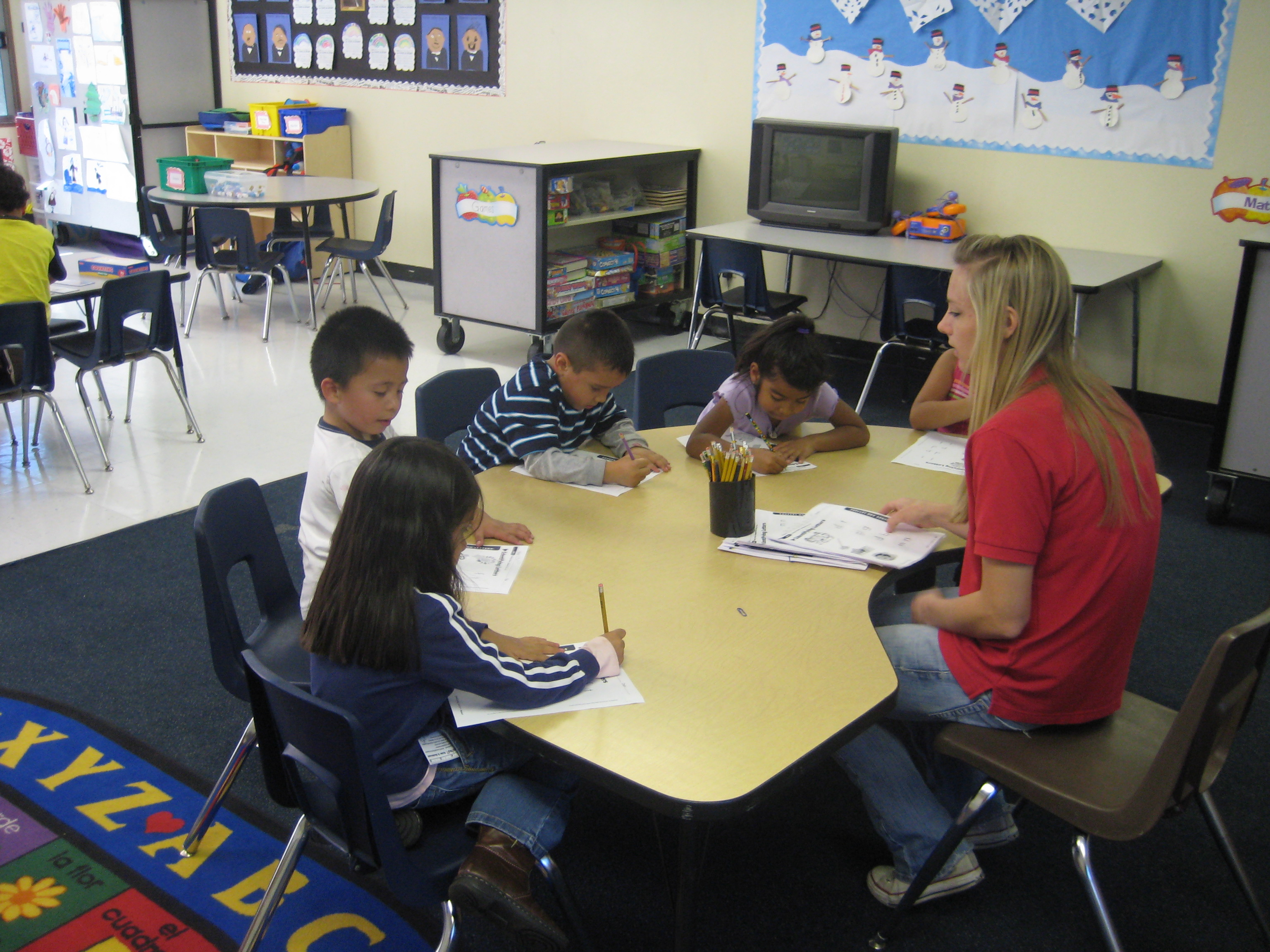 students working at a table with teacher