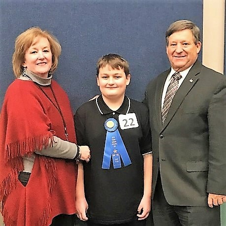 Spelling Bee winner stands with Superintendent and Principal