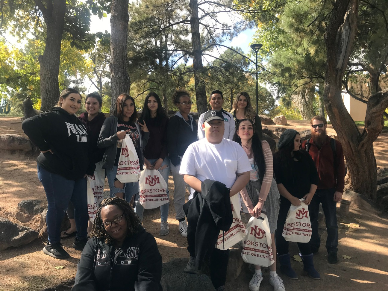 Students standing outside with UNM Bookstore bags