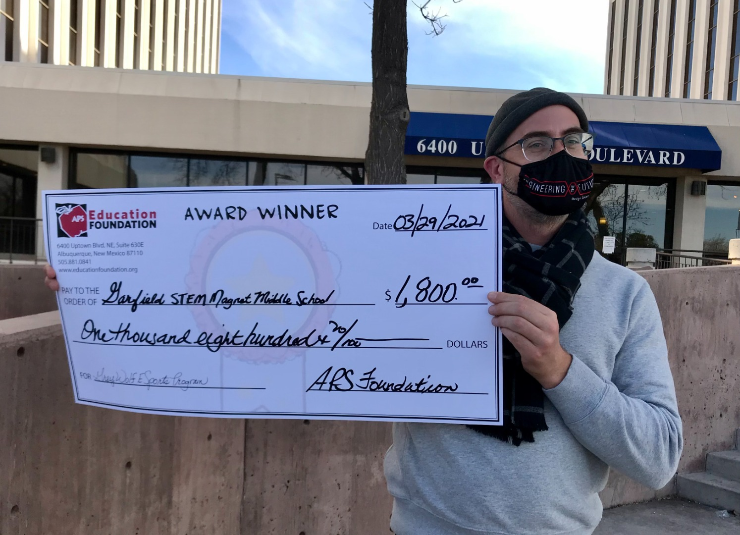 Joshua LaClair holding up his APS Foundation big check to help fund his esports  gaming club