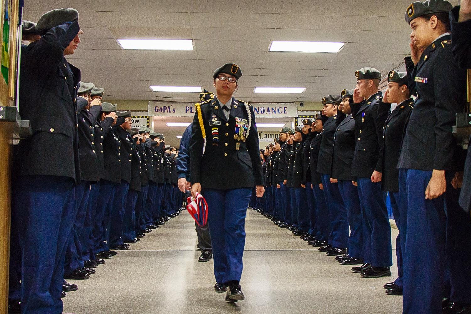 Cadets are lined up on both sides of the hallway as the Color Guard march in  with the flag.
