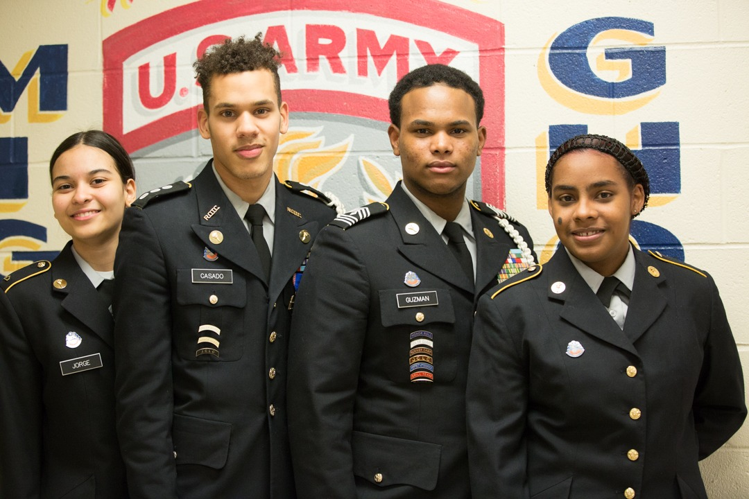 Cadets standing in hallway standing in front of the Army Shield.