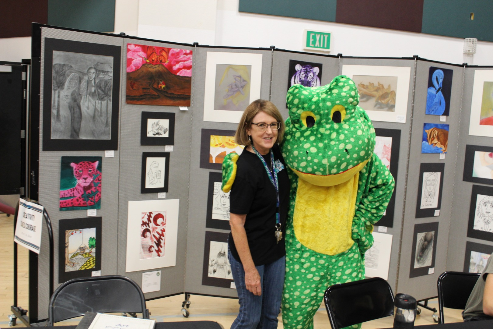 Teacher standing with the frog mascot in front of student art display