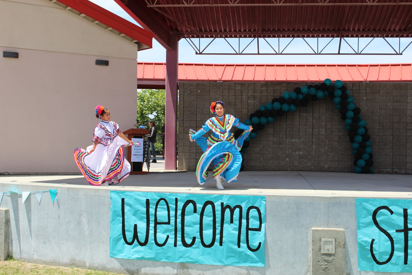 ballet folklórico students dancing on stage in dresses