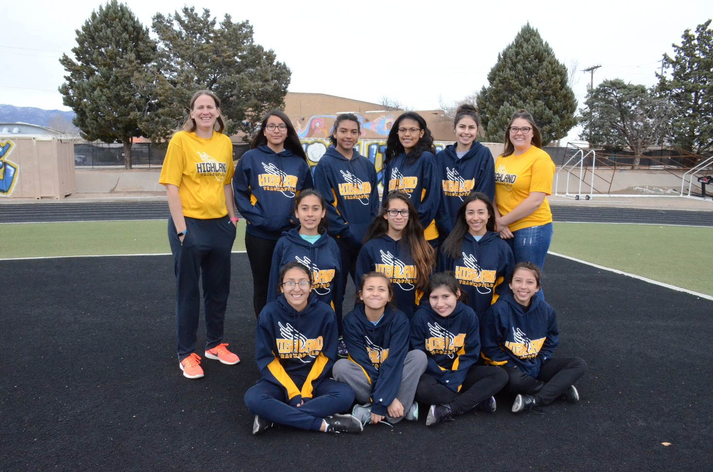 Group photo of girls track team with coach