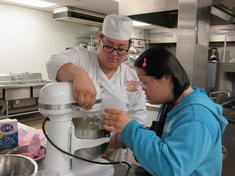 Culinary arts students using a cake mixer