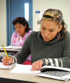 Female adult student reading to take notes