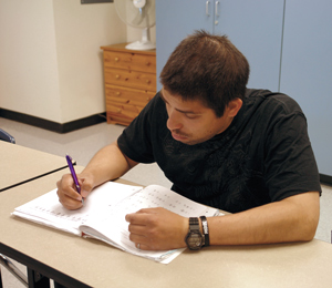 Male adult student working at desk