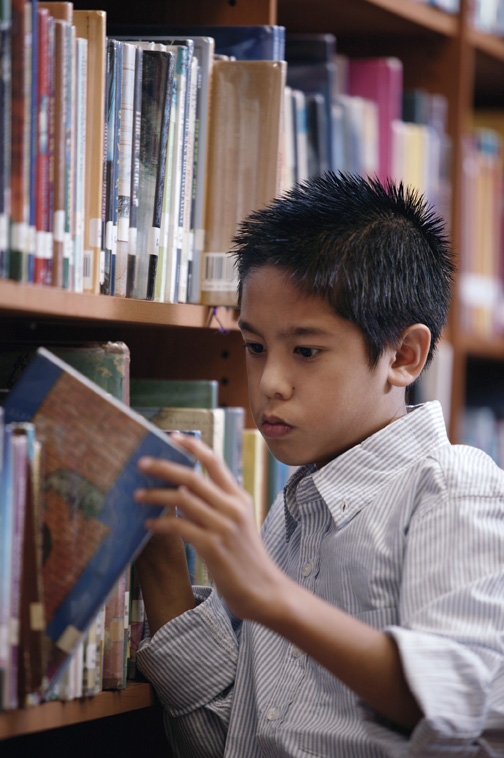 asian boy choosing book