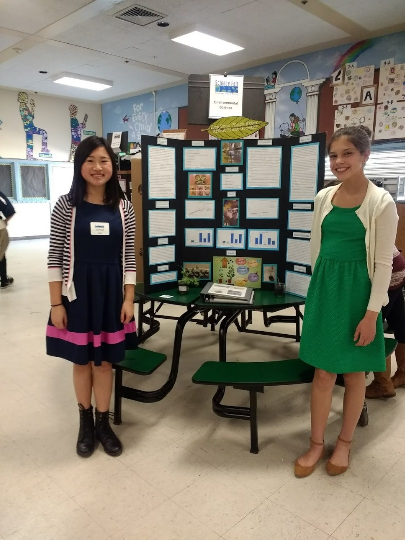 Two 7th-grade students with their Science Fair display