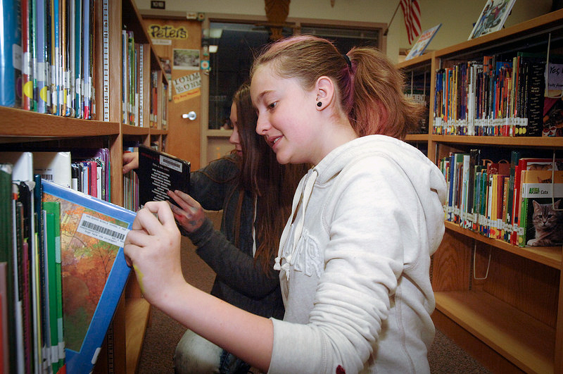 Student selects a book off the shelf in a library