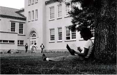 girl reading a book under a tree