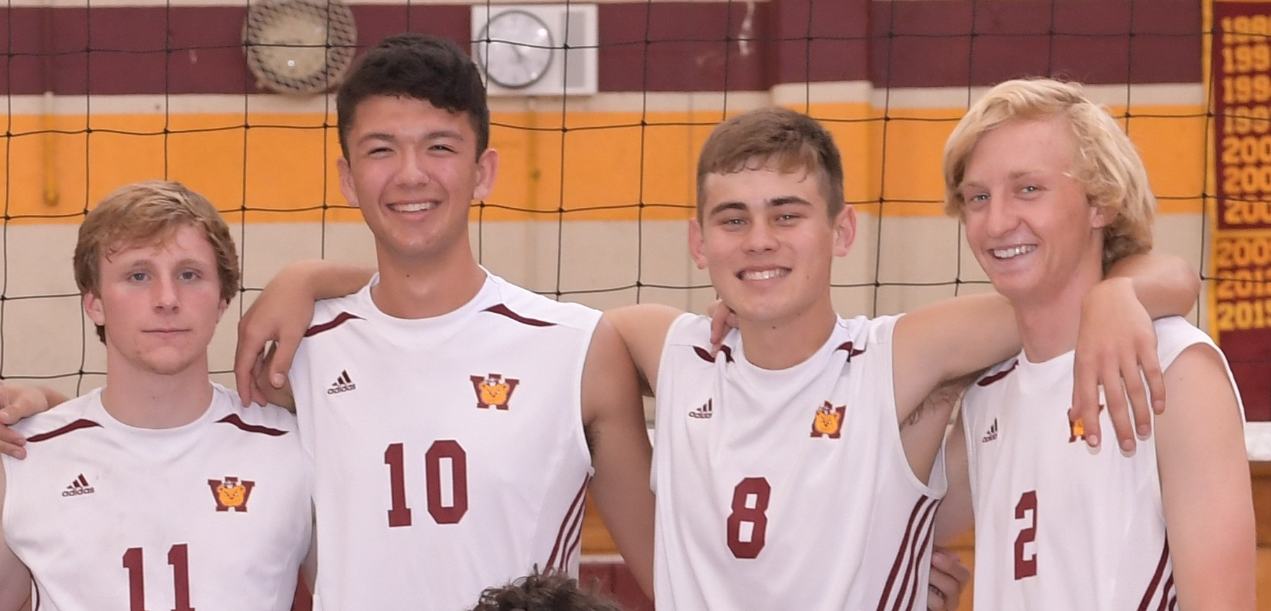 boys volleyball team smile for a photo