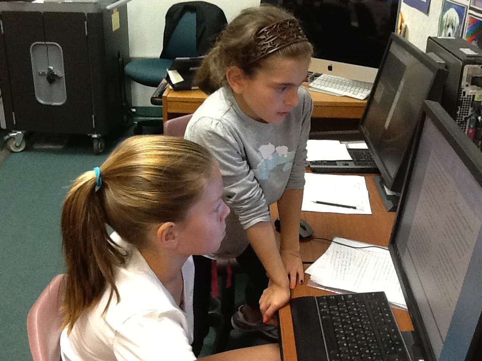 Two students working together on one computer