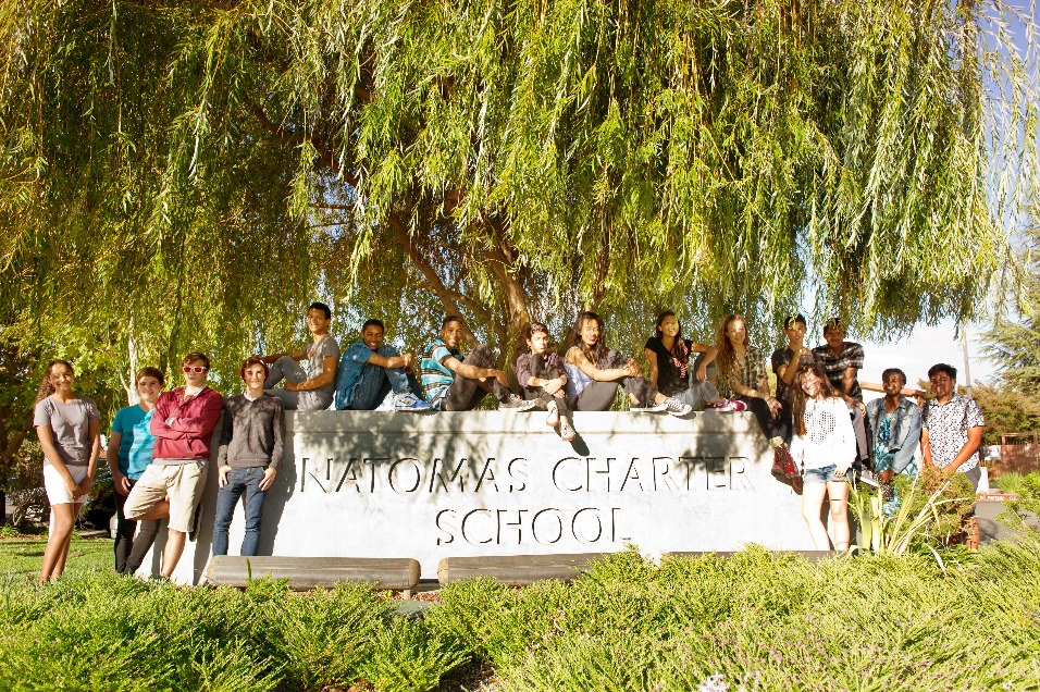 School sign with students surrounding
