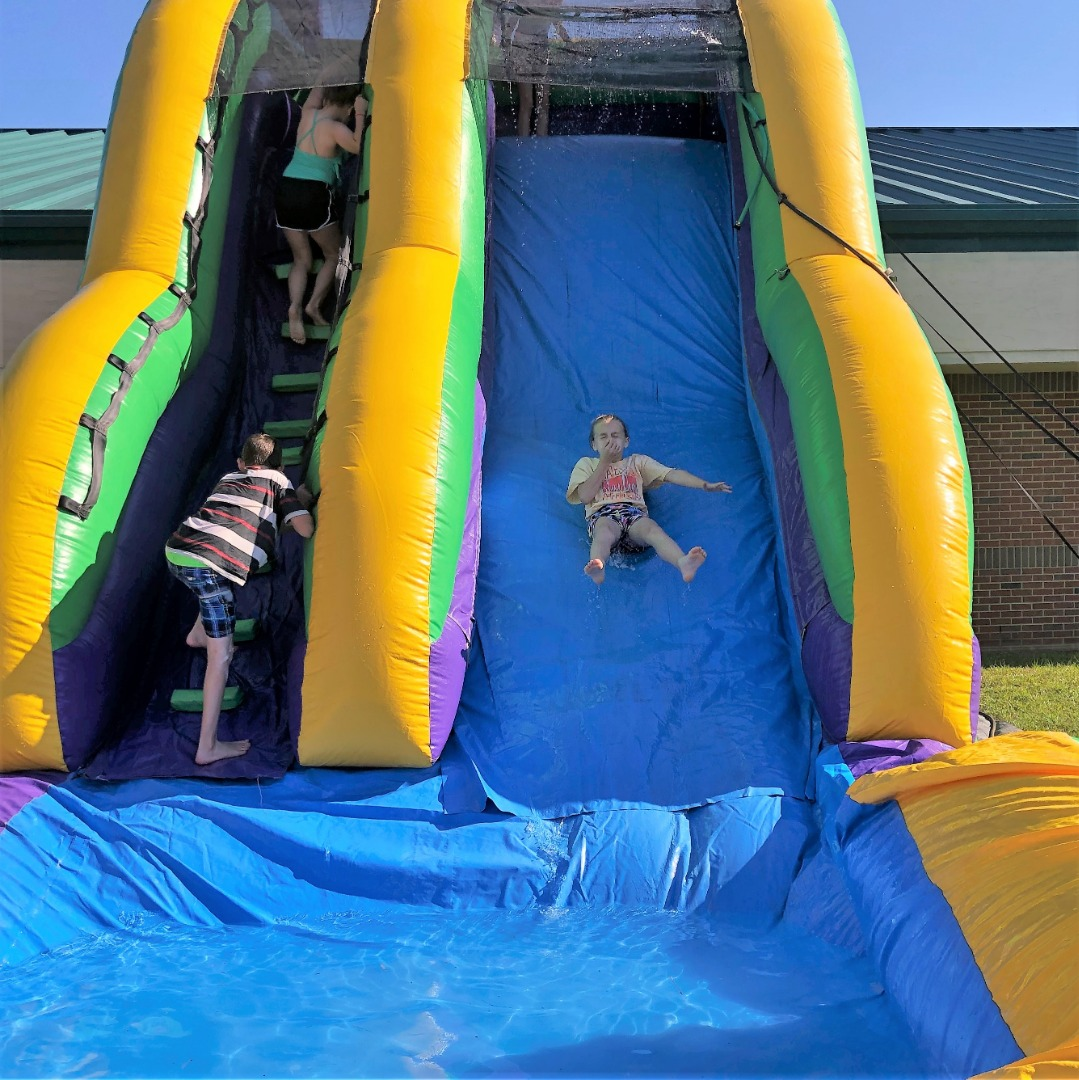 student on slide from water day
