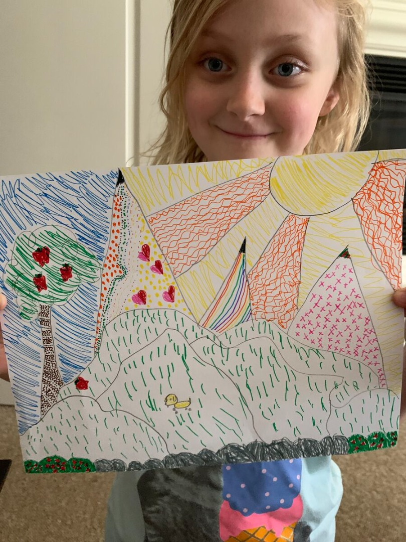 Student holding up her art, colorful line landscape drawing