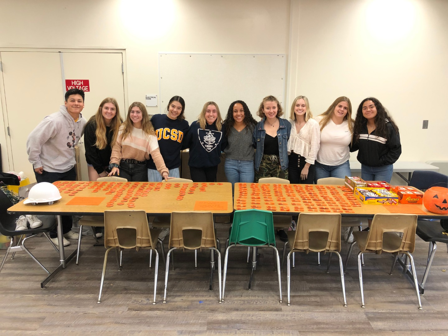 ten students standing behind a table of orange buttons