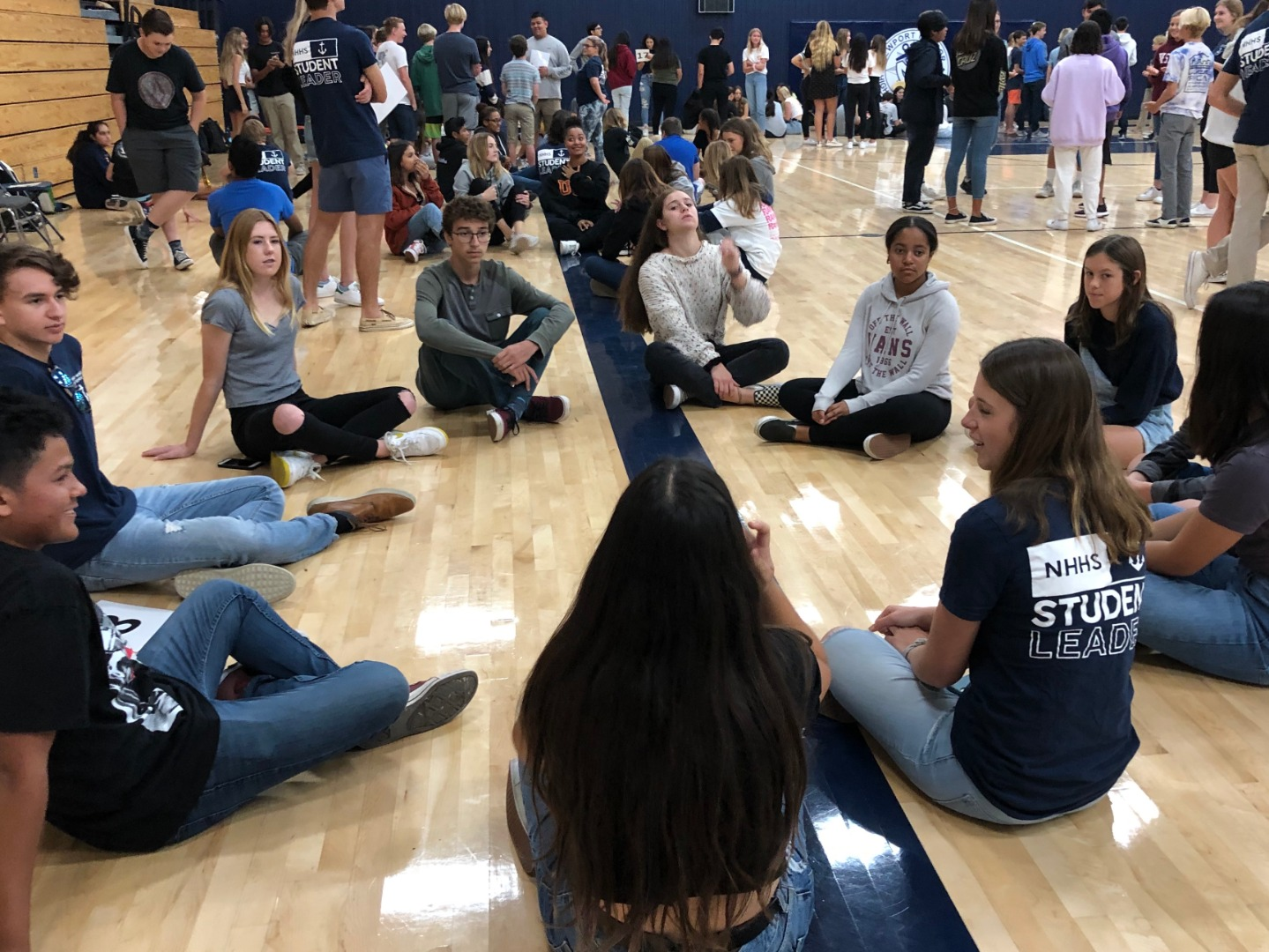 students sitting in a circle in the gym