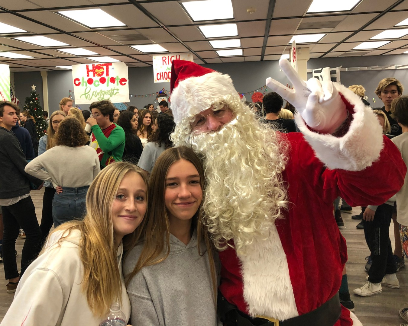 Santa Claus and two female students smiling