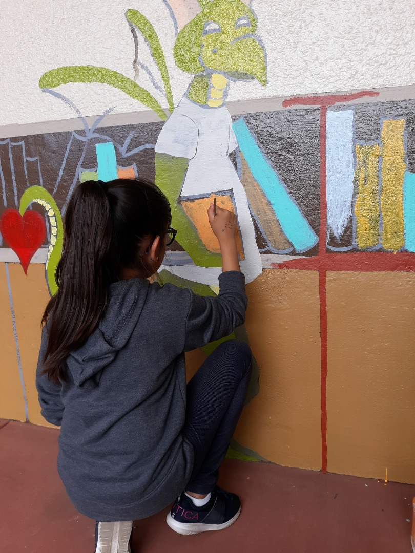 Student Painting the Library Mural