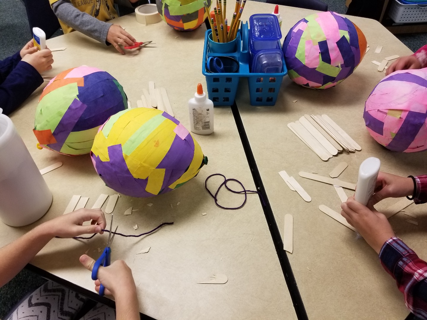 Students make hot air balloons from paper mache and tissue paper.