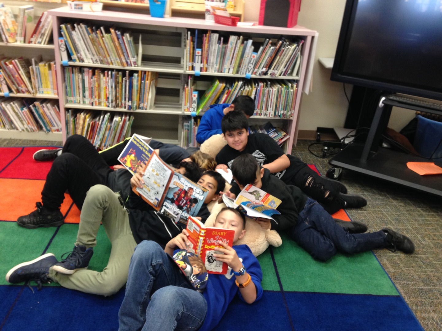 Students laying on the floor reading books