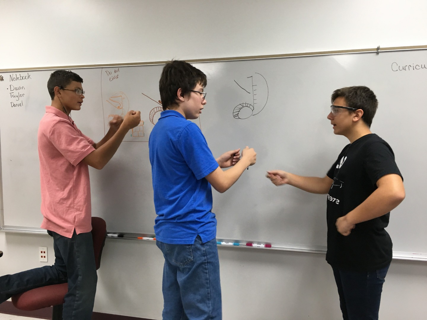 Taylor McLain, Davin Gould, and Daniel Thele plan their robot.