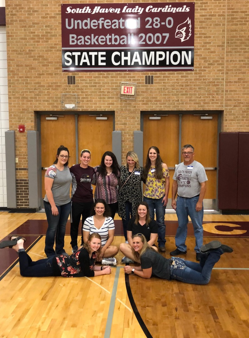 The 1997 Girls Basketball Team with their wall banner.