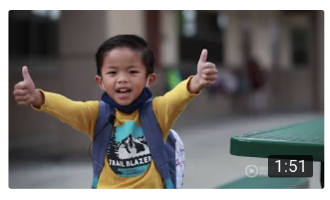 Boy with arms outreached and thumbs up