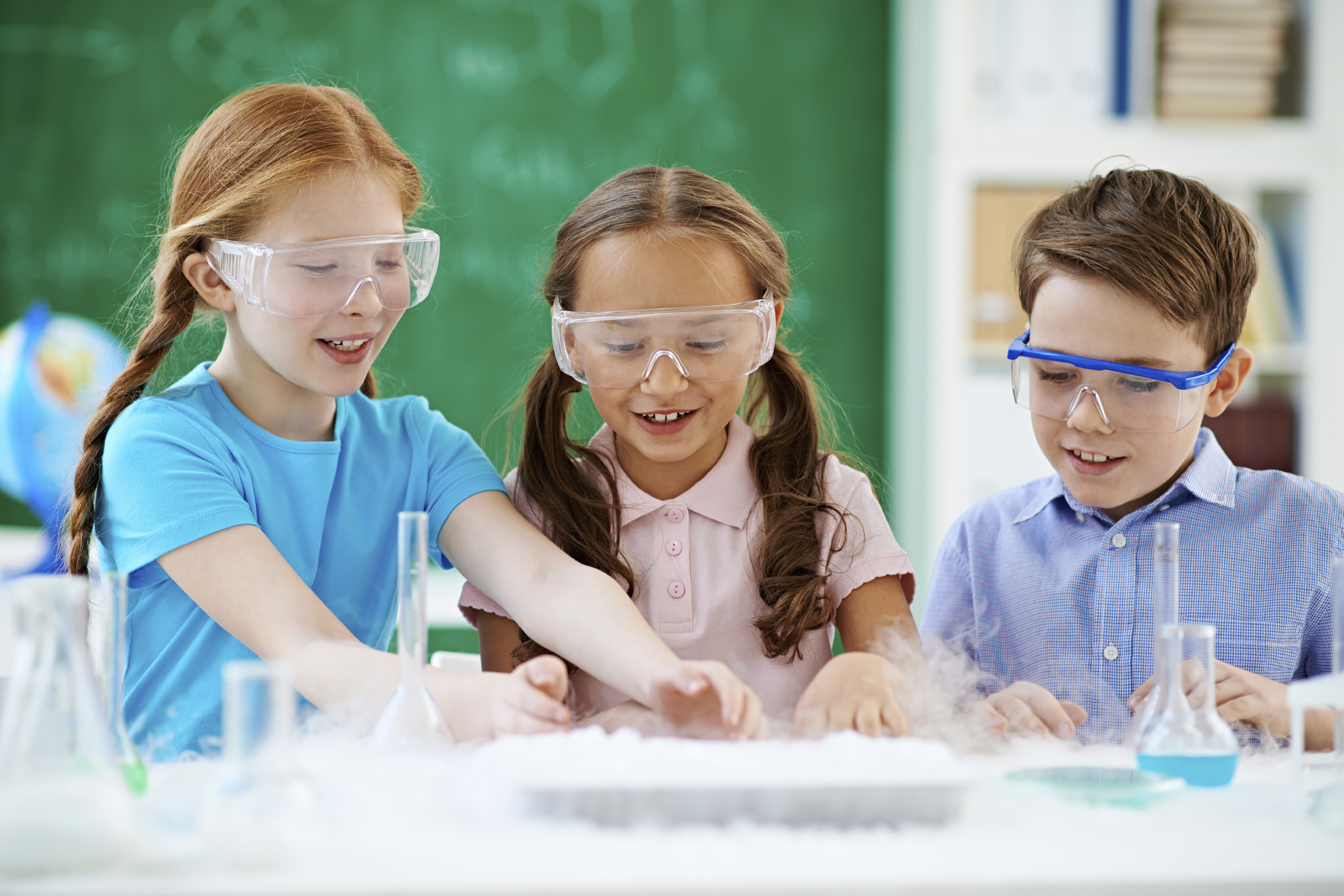 Elementary students wearing safety glasses working on science